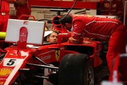 Sebastian Vettel, Ferrari, talks to a colleague from the cockpit of his car, which is fitted with a