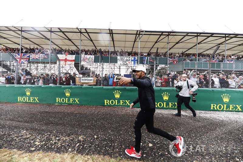 Lewis Hamilton, Mercedes AMG F1, runs past fans in a grandstand while filming them on his phone