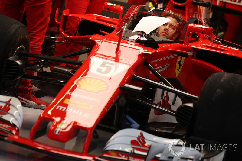 Sebastian Vettel, Ferrari, sits in the cockpit of his car, which is fitted with a new protective windscreen shield