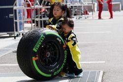 De jeunes fans de Renault Sport F1 Team avec un pneu Pirelli