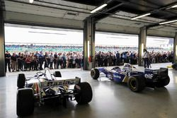 Fans view a garage filled, classic Williams F1 machinery
