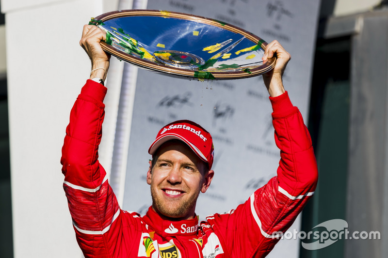 Sebastian Vettel, Ferrari, 1st Position, holds his trophy aloft