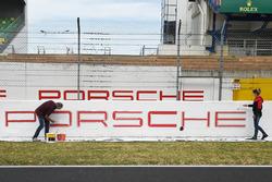 La peinture des publicités Porsche au bord du circuit