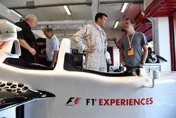 Piloto en el coche de dos asientos de la experiencia de la F1 Will Buxton, NBC TV Presentador y Fran
