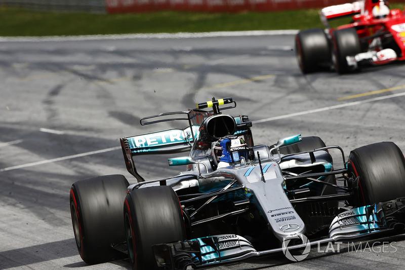 Valtteri Bottas, Mercedes AMG F1 W08, raises an arm in victory celebration at the finish, ahead of Sebastian Vettel, Ferrari SF70H