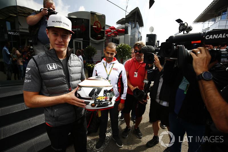 Stoffel Vandoorne, McLaren, displays a Bell helmet in front of media