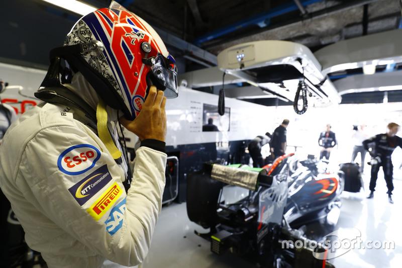 Jenson Button, McLaren puts on his helmet in the garage