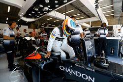 Fernando Alonso, McLaren lowers himself into the cockpit.