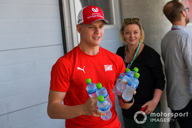 Mick Schumacher, brings the media bottles of water