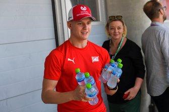 Mick Schumacher, brings the media bottles of water