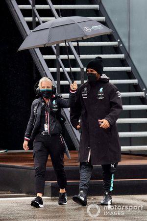 Angela Cullen, Physio for Lewis Hamilton, holds an umbrella over Lewis Hamilton, Mercedes