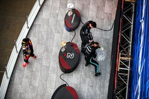 Max Verstappen, Red Bull Racing, 2nd position, Lewis Hamilton, Mercedes, 1st position, and the Mercedes team representative spray Champagne on the podium