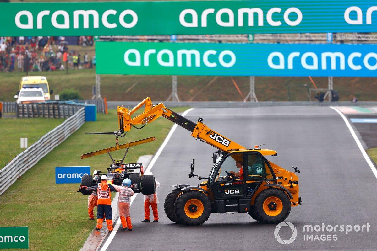 Los oficiales de pista retiran el coche dañado de Sergio Pérez, Red Bull Racing RB16B