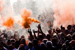 Fans steken oranje rook af op de tribunes