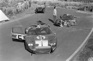 The damaged cars of Frank Gardner, Roger McCluskey, Holman Moody Racing, Ford GT40 Mk2B, and Mario Andretti, Lucien Bianchi, Holman Moody Racing, Ford GT40 Mk4, with a Willys Jeep of the fire service