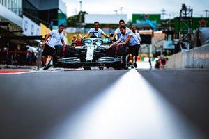 Mecánicos de Mercedes empujando el coche a lo largo del pit lane