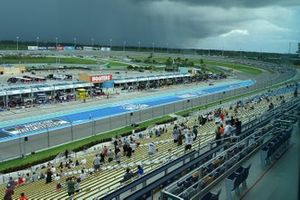 Race start with fans in the grandstand and big clouds approaching