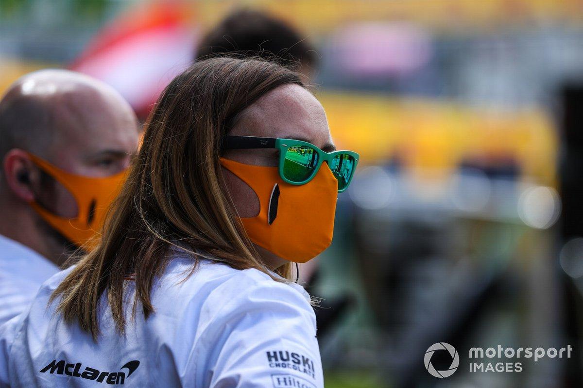 A McLaren team member wears a mask on the grid