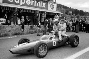Giancarlo Baghetti, BRM P57 le da a Phil Hill, Cooper y a Andre Pilette, Scirocco un aventón de vuelta a los pits