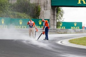Marshals work with cement dust to dry the track