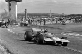 Jack Brabham, Brabham BT33 Ford, passes marshals working to extinguish a blazing car