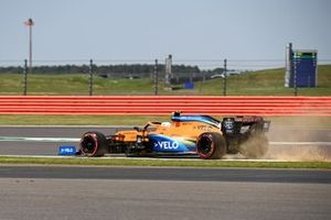 Lando Norris, McLaren MCL35, kicks up dust and sparks