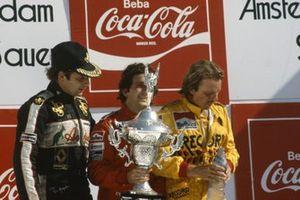 Alain Prost, 1st position, holds his trophy alongside Keke Rosberg, 2nd position, and Elio de Angelis, 3rd position