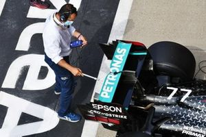 An FIA delegate inspects the car of Valtteri Bottas, Mercedes F1 W11, in Parc Ferme