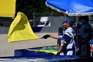 A Marshal waves a yellow flag