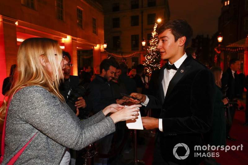 George Russell signs an autograph for a fan