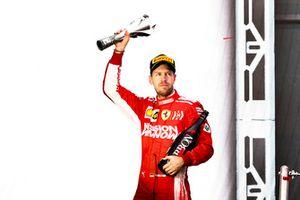 Sebastian Vettel, Ferrari, deuxième, avec le champagne et son trophée sur le podium