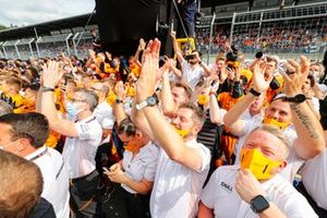 The McLaren team cheer for their driver on the podium