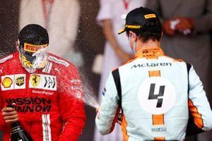 Carlos Sainz Jr., Ferrari, 2nd position, and Lando Norris, McLaren, 3rd position, spray Champagne on the podium