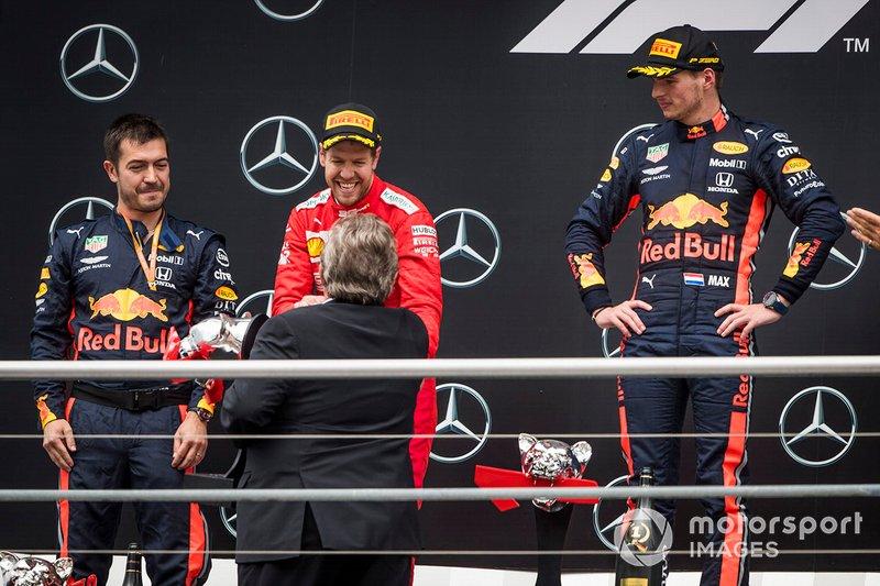 Sebastian Vettel, Ferrari, 2nd position, receives his trophy alongside Max Verstappen, Red Bull Racing, 1st position, on the podium