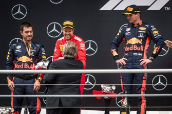 Sebastian Vettel, Ferrari, 2nd position, receives his trophy alongside Max Verstappen, Red Bull Racing, 1st position, on the podium