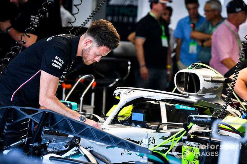 Engineer installs new livery on the Halo of the Mercedes AMG F1 W10