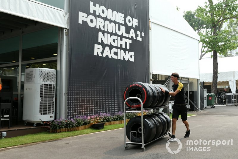 A Renault team member pushes Pirelli tyres on a trolley in the paddock