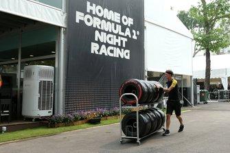 Un membro del team Renault spinge i pneumatici Pirelli su un trolley nelpaddock