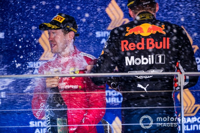 Sebastian Vettel, Ferrari, primo classificato, e Max Verstappen, Red Bull Racing, terzo classificato, spruzza Champagne sul podio