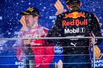 Sebastian Vettel, Ferrari, 1st position, and Max Verstappen, Red Bull Racing, 3rd position, spray Champagne on the podium