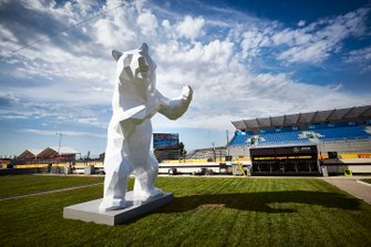A large bear sculpture by the side of the track
