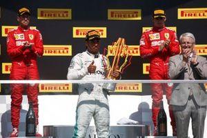 Sebastian Vettel, Ferrari, 2nd position, Lewis Hamilton, Mercedes AMG F1, 1st position, with his trophy, and Charles Leclerc, Ferrari, 3rd position, on the podium