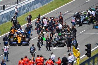 Lando Norris, McLaren MCL34, Romain Grosjean, Haas F1 Team VF-19, en la parrilla