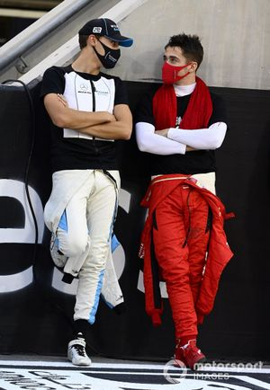 George Russell, Williams Racing, talks with Charles Leclerc, Ferrari