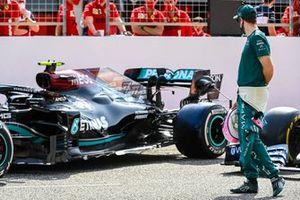 Sebastian Vettel, Aston Martin, looks at the car of Valtteri Bottas, Mercedes W12