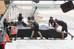 Mechanics push the car of Lewis Hamilton, Mercedes W12, into the garage