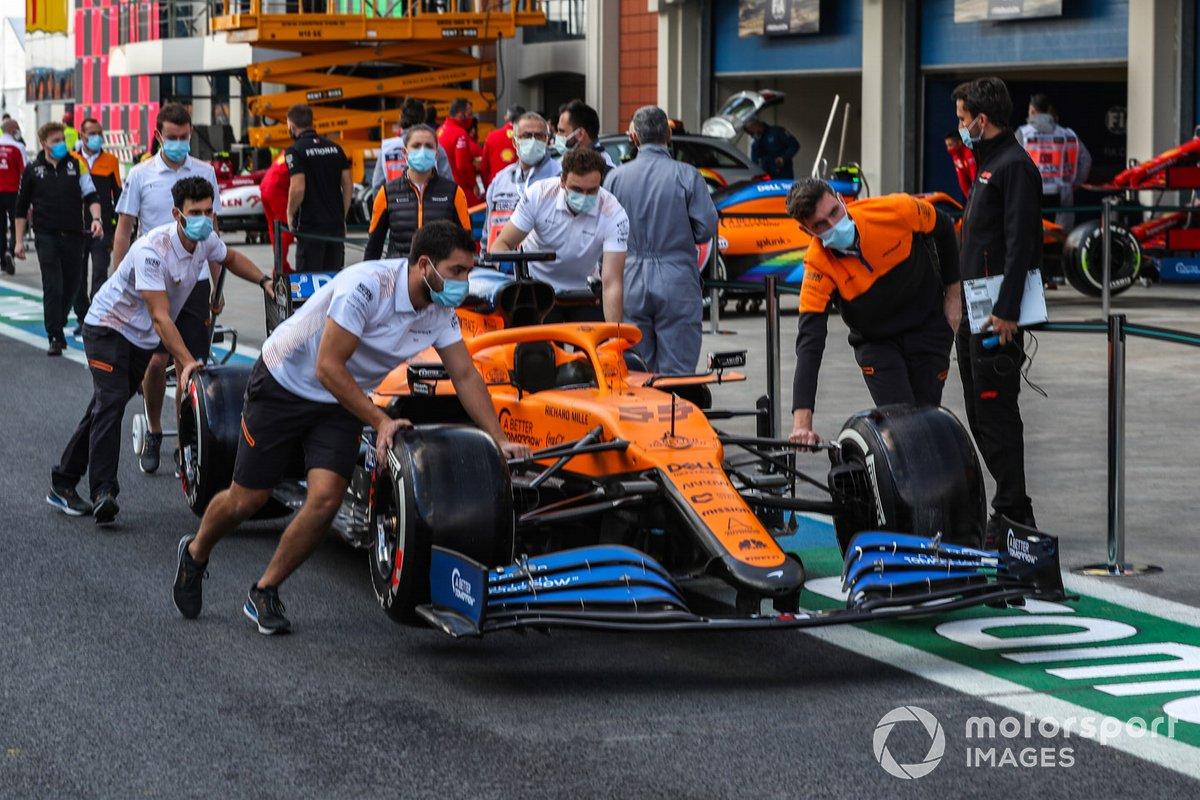 Mecánicos de McLaren llevan el coche por el pitlane de Turquía