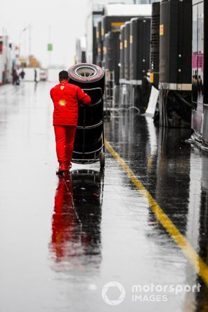 Pirelli tires being pushed by a Ferrari team member in the paddock