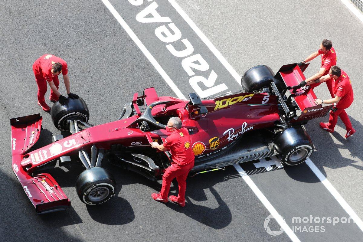 Membri del team Ferrari spingono la vettura di Sebastian Vettel Ferrari SF1000 in pit lane