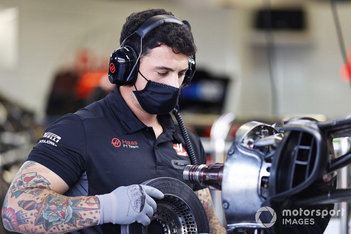 Haas team member works on brakes